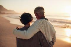 花费从容不迫的时间的资深夫妇在海滩上 免版税库存图片