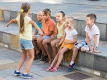花费时间外部和演奏凭动作猜字谜游戏的孩子画象  图库摄影