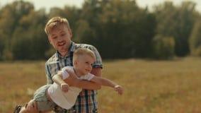 花费时间本质上的年轻家庭 微笑在照相机的妇女 转动他的胳膊的父亲儿子 影视素材