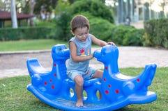 花费时间的微笑的愉快的矮小的男婴使用与蓝色龙的公园 免版税库存照片