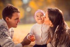花费时间的愉快的年轻家庭室外在秋天公园 图库摄影