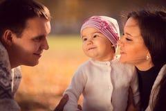 花费时间的愉快的年轻家庭室外在秋天公园 免版税库存图片