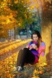 花费时间的美丽的妇女在公园在秋天季节期间 图库摄影