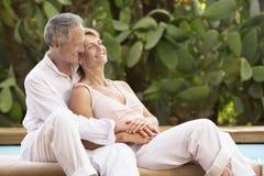 花费浪漫时间的夫妇由水池 免版税库存照片