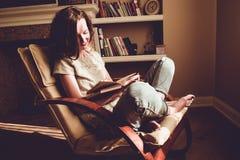 花费由阅读书的业余时间 家和舒适概念 妇女微笑读在舒适的现代椅子的有趣的书 n 图库摄影