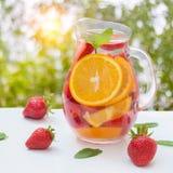 芳香化的水用新鲜的草莓和薄菏在一个玻璃水罐 库存图片