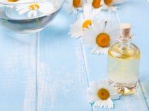 芳香在蓝色木背景的油和春黄菊花 免版税库存照片