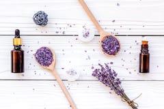 芳香疗法为放松概念 淡紫色分支、温泉盐、油和蜡烛在白色背景顶视图 免版税库存照片