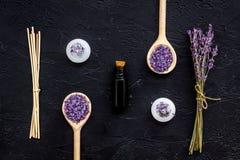 芳香疗法为放松概念 淡紫色分支、温泉盐、油和蜡烛在黑背景顶视图 免版税库存图片