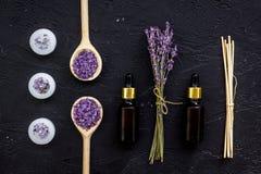 芳香疗法为放松概念 淡紫色分支、温泉盐、油和蜡烛在黑背景顶视图 库存照片