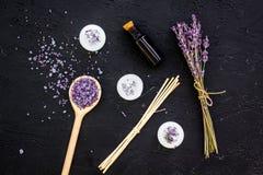 芳香疗法为放松概念 淡紫色分支、温泉盐、油和蜡烛在黑背景顶视图 免版税图库摄影
