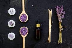 芳香疗法为放松概念 淡紫色分支、温泉盐、油和蜡烛在黑背景顶视图 库存图片