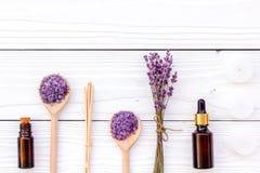芳香疗法为放松概念 淡紫色分支、温泉盐和油在白色木背景顶视图copyspace 免版税图库摄影