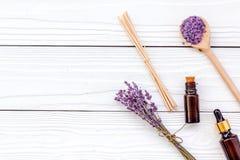 芳香疗法为放松概念 淡紫色分支、温泉盐和油在白色木背景顶视图copyspace 免版税库存图片
