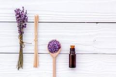 芳香疗法为放松概念 淡紫色分支、温泉盐和油在白色木背景顶视图copyspace 库存照片