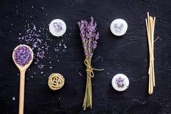 芳香疗法为放松概念 淡紫色分支、温泉盐和蜡烛在黑背景顶视图 免版税图库摄影