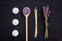 芳香疗法为放松概念 淡紫色分支、温泉盐和蜡烛在黑背景顶视图 免版税库存照片