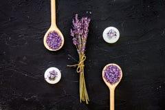 芳香疗法为放松概念 淡紫色分支、温泉盐和蜡烛在黑背景顶视图 库存图片