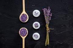 芳香疗法为放松概念 淡紫色分支、温泉盐和蜡烛在黑背景顶视图 库存照片