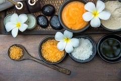 芳香疗法和糖和盐按摩的温泉泰国设置与在床上的花,放松和健康关心 免版税库存照片