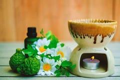 芳香疗法在木桌上的精油燃烧器用香柠檬和花 免版税库存图片