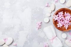 芳香疗法,秀丽,与按摩小卵石的温泉背景,充满了香气花浇灌和在石台式视图的蜡烛 平的位置 免版税库存图片