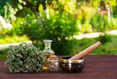 芳香麝香草、精油和唱歌碗 要素私有放松阵雨温泉 草本和油在绿色弄脏了背景 库存图片