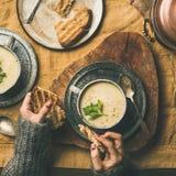 芹菜奶油汤和女性手用面包,方形的庄稼 免版税库存图片
