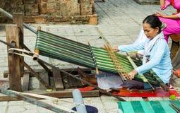 芽庄市,省可汗Khoa,越南, 2017年6月08日:一名年长越南妇女,织布工,坐在一台编织机并且编织a 免版税图库摄影