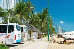 芽庄市,越南- 2019年4月11日:人在海滩的路面去与棕榈,并且公共汽车在假期依靠 库存图片
