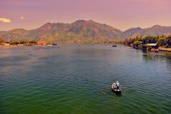 芽庄市,越南- 2013年5月02日, :渔夫和他的妻子在海驾驶小船 免版税库存图片