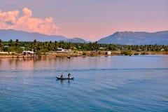 芽庄市,越南- 2013年5月02日, :渔夫和他的妻子驾驶小船到鱼在海村庄 库存照片