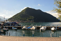 苏尔扎诺,意大利- 2017年5月13日:苏尔扎诺镇港口有小船的在有蒙泰伊索拉的背景的,意大利湖Iseo 免版税库存图片