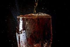苏打大玻璃,溢出的杯与在黑色隔绝的泡影的苏打特写镜头 免版税库存图片