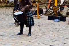 苏格兰战士,战士,传统服装的音乐家有裙子的打在中世纪老城堡的正方形的鼓 免版税库存图片