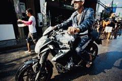 苏梅岛,泰国- 4月13 :水战斗节日或Songkran节日的未认出的肮脏的骑自行车的人 免版税图库摄影