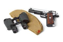 苏联军队士兵草料盖帽、双筒望远镜和手枪 免版税库存图片