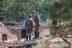 苏联士兵准备晚餐 敌意2018-04-30翼果地区,俄罗斯的重建 免版税库存照片