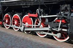 苏联时期的老黑蒸汽机车的轮子 机车的边有转动的技术的元素的  免版税库存照片