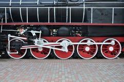 苏联时期的老黑蒸汽机车的轮子 机车的边有转动的技术的元素的  免版税图库摄影