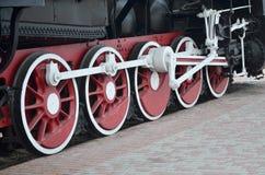 苏联时期的老黑蒸汽机车的轮子 机车的边有转动的技术的元素的  免版税库存图片