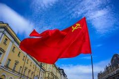 苏维埃社会主义共和国的一面红旗有挥动在风的锤子和镰刀的在国际工作者`天 免版税库存图片