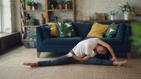 苗条亚裔夫人在家做着舒展身体、胳膊和腿在供以座位的位置的体育在地板享受活动 影视素材