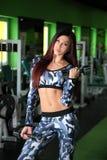 苗条女孩改正在健身房的图 与哑铃的锻炼 免版税图库摄影