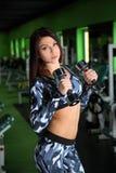 苗条女孩改正在健身房的图 与哑铃的锻炼 库存照片