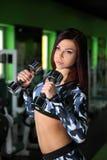 苗条女孩改正在健身房的图 与哑铃的锻炼 免版税库存照片