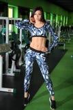 苗条女孩改正在健身房的图 训练在图的更正健身房 免版税库存照片