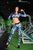 苗条女孩改正在健身房的图 训练在图的更正健身房 图库摄影