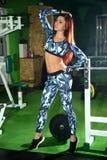 苗条女孩改正在健身房的图 训练在图的更正健身房 免版税库存图片