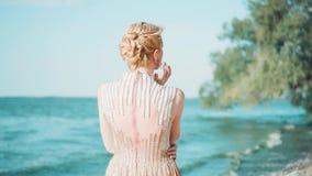 苗条女孩站立回到照相机,穿戴在太阳的浅粉红色的豪华昂贵的发光的礼服 薄纱火车,白肤金发 股票录像